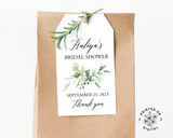 Lux Party's white bridal shower favor tag with black script and greenery leaves, affixed to a brown kraft favor bag.