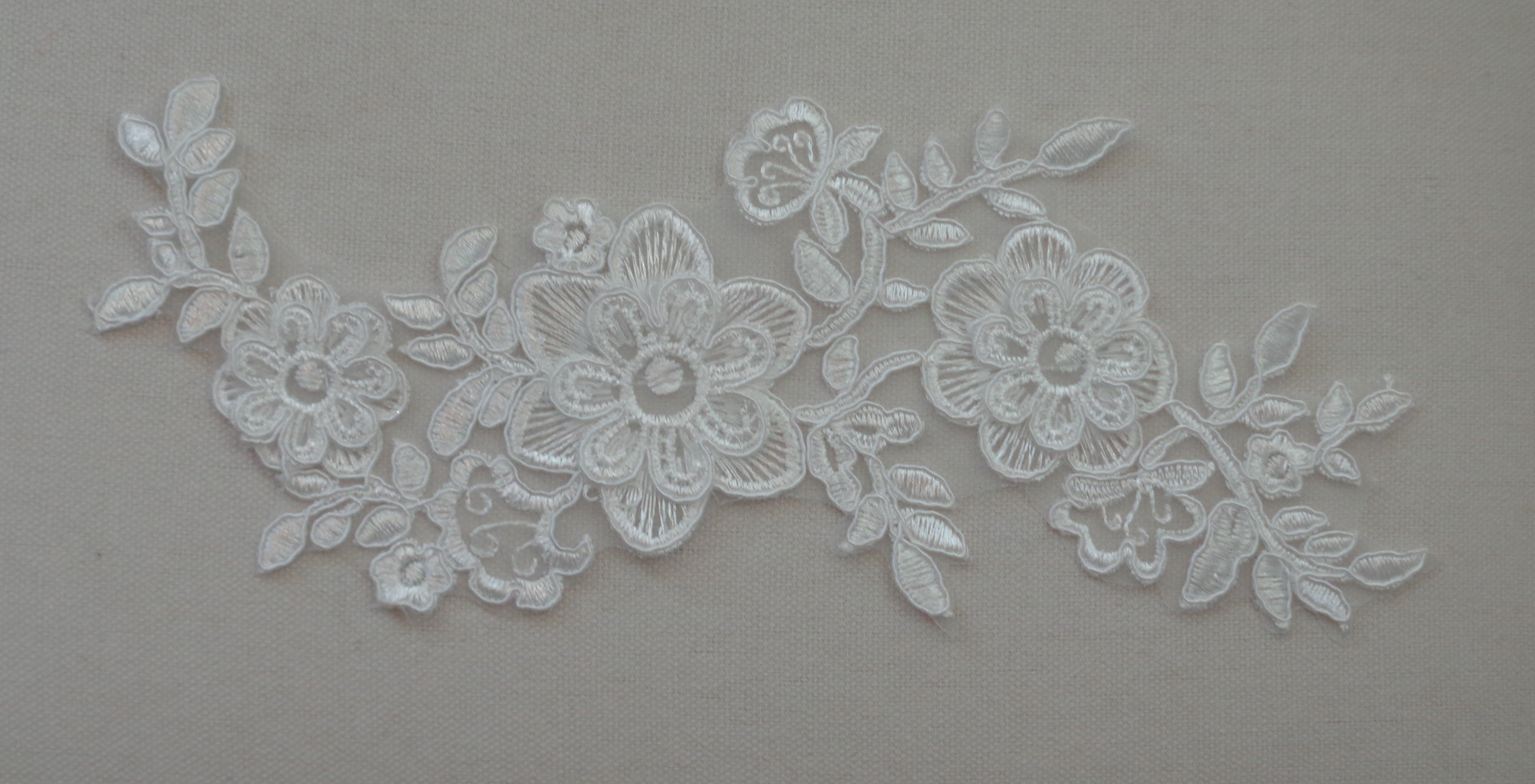 A piece of d floral layers ivory lace applique on organza