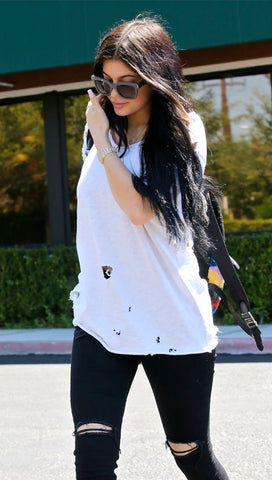 Kylie Jenner in black skinny cut out knee jeans