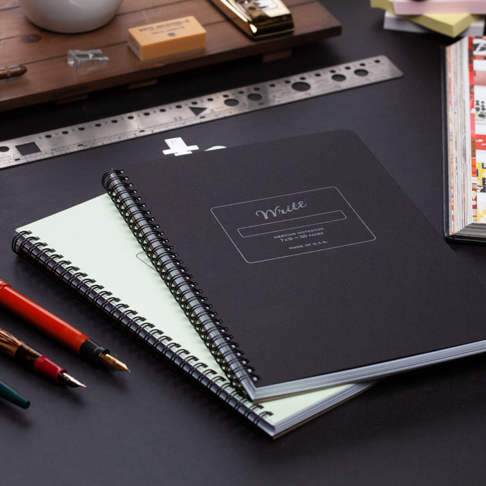 2 meeting notebooks on an executive's desk
