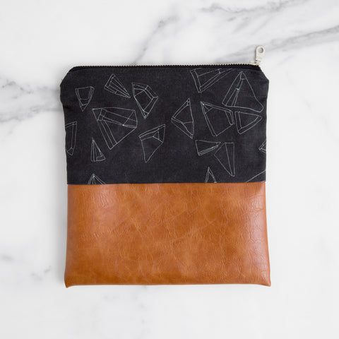 black hollow pouch with zipper - sideview laying on marble; made in usa by allie kushnir | carpenter hill