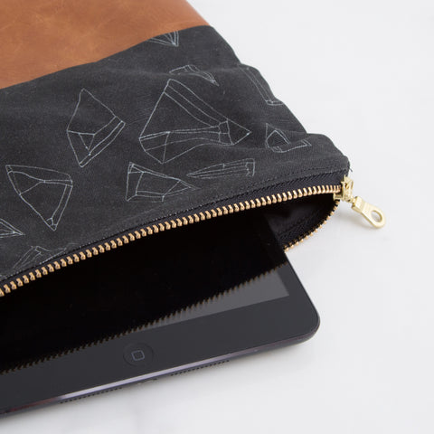 black hollow pouch with zipper - closeup sideview laying on marble with digital device; made in usa by allie kushnir | carpenter hill