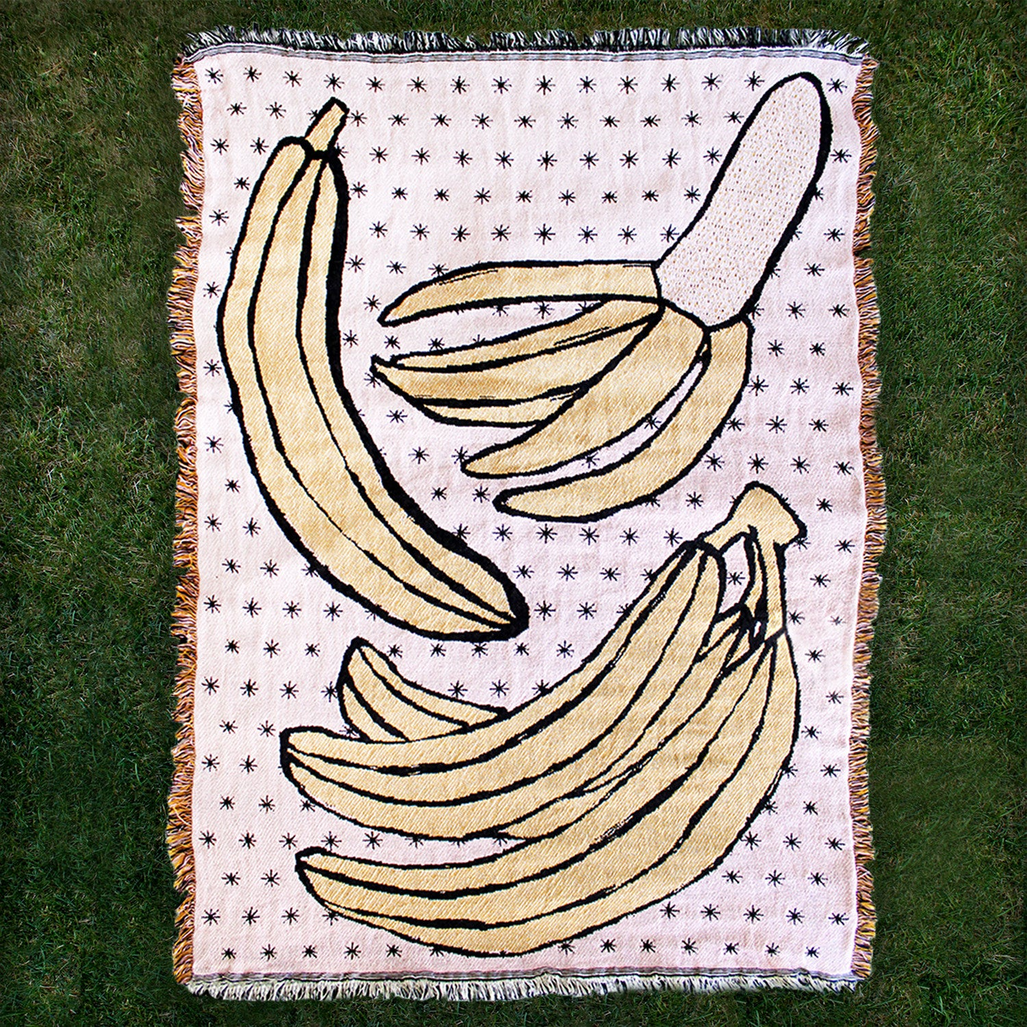 throw blanket with bananas, bright colors - overhead view laying flat on grass; made in usa by calhoun & company | carpenter hill