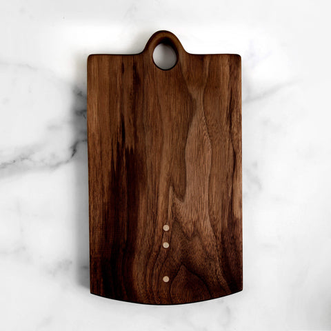 "walnut cutting board - 10 x 6 with 1"" handle - shown laying on marble slab; made in usa by two tree studios 
