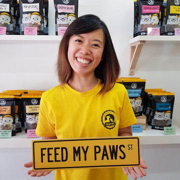 Clarissa from Feed My Paws holding a Feed My Paws Street Sign at Toa Payoh Outlet in Singapore