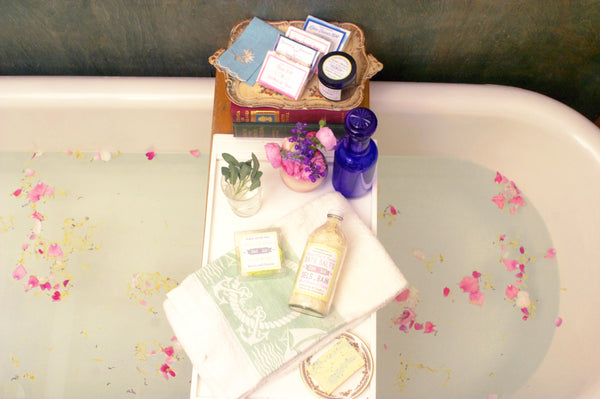antique bathtub with vintage apothecary products