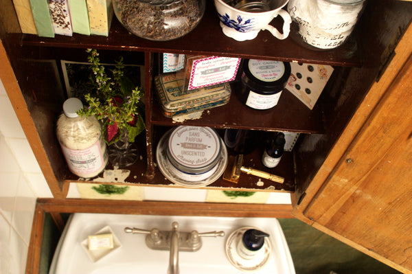 vintage beauty apothecary cabinet in a romantic bathroom