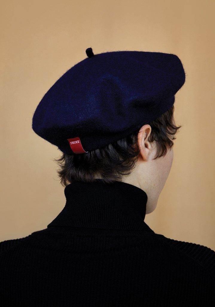 person wearing feministe beret, facing back