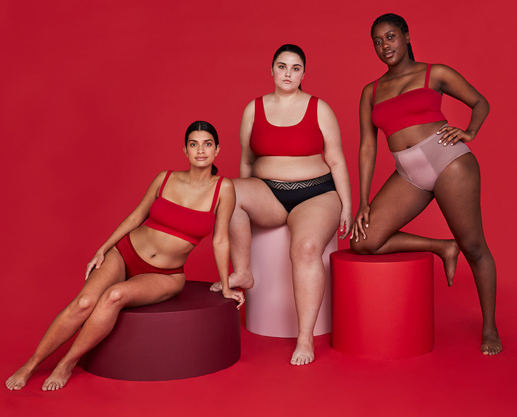 wide image with three women modeling Thinx Hiphugger in Black, Thinx Hi-Waist in Dusk and Thinx Cheeky in Crimson