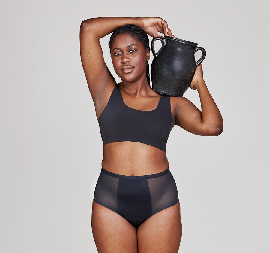 a woman holding a jug. The woman is modeling Thinx Super Hi-Waist in Black
