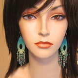 Turquoise enamel and crystal chandelier earrings on a mannequin