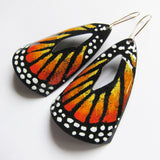 Close-up of orange enamel butterfly earrings on kidney wires