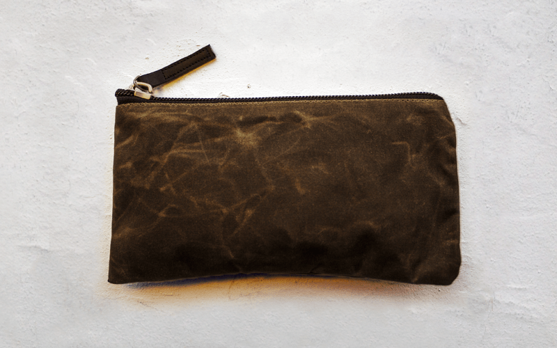 The Dessie case is a waxed cotton EDC wallet pouch made with vegetable tanned leather detail