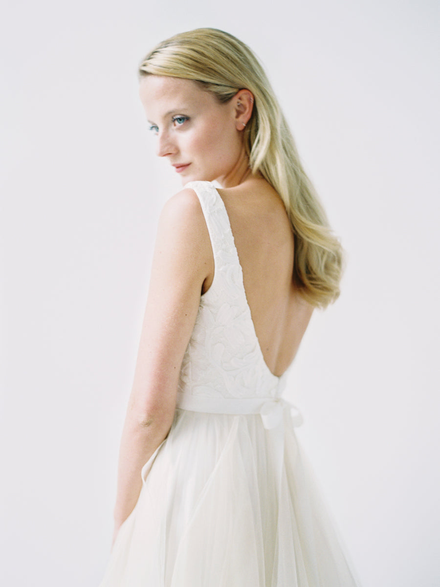 A scoop neck wedding gown with a delicate corded lace and a low back