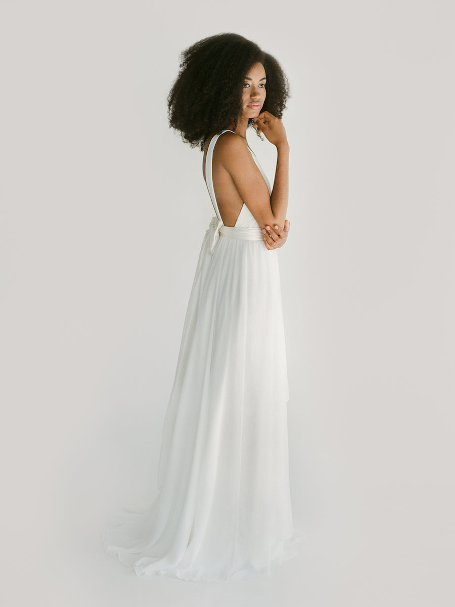 A simple backless wedding dress with a deep v and a hi-lo skirt