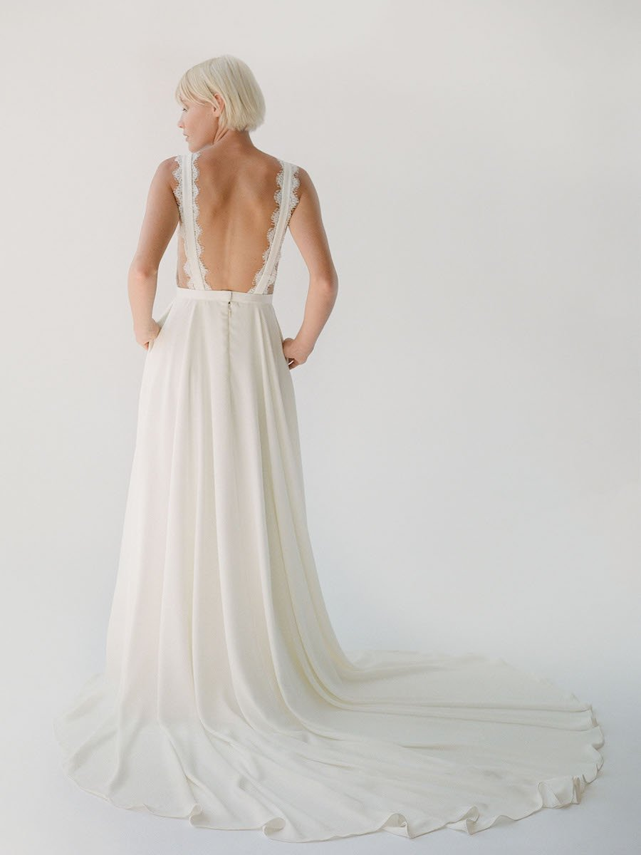 Crepe wedding dress with an open back, long train, and pockets