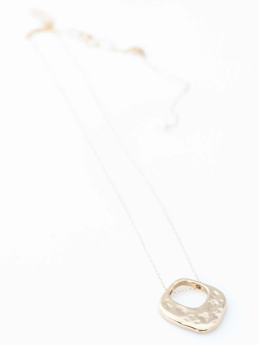 Hammered brass cutout necklace with a single pearl