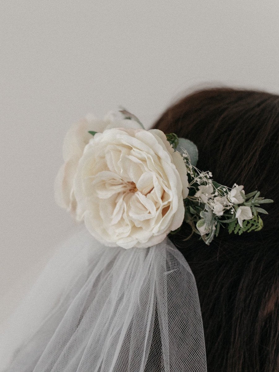 A bridal hair comb made with silk roses and ivory baby's breath