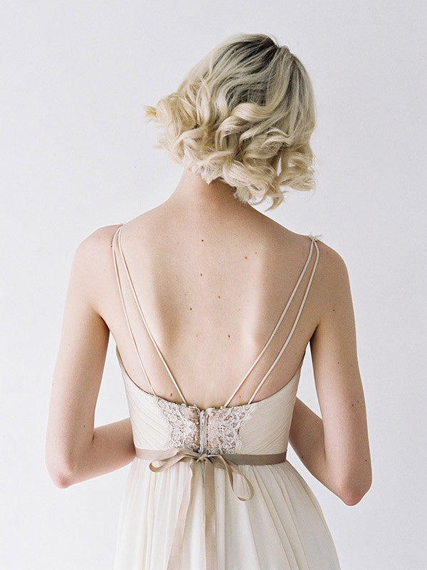 A low-back wedding gown with double straps