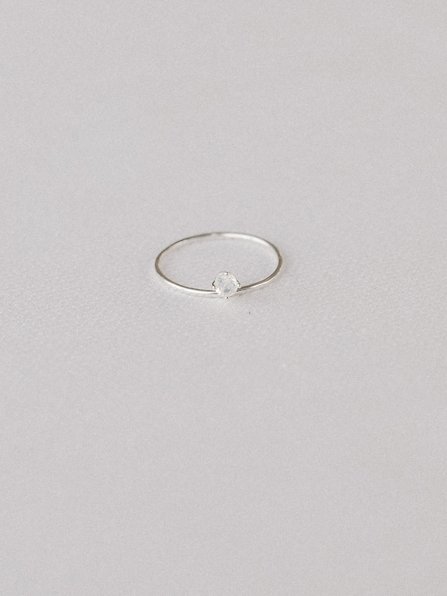 Simple sterling silver stacking ring featuring a single rainbow moonstone