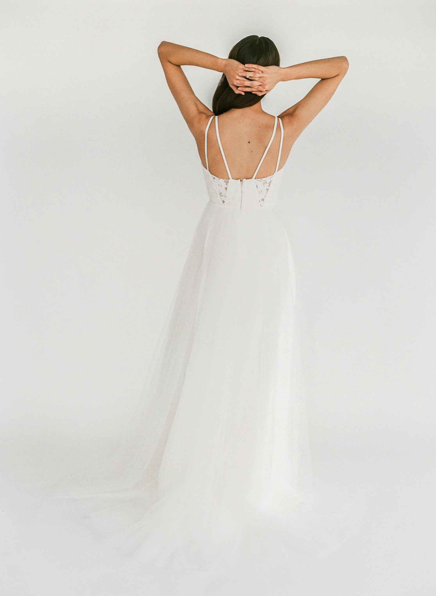 Ethical handmade wedding gown with beaded lace, sheer geometric cutouts, comfortable double straps, and a tulle skirt