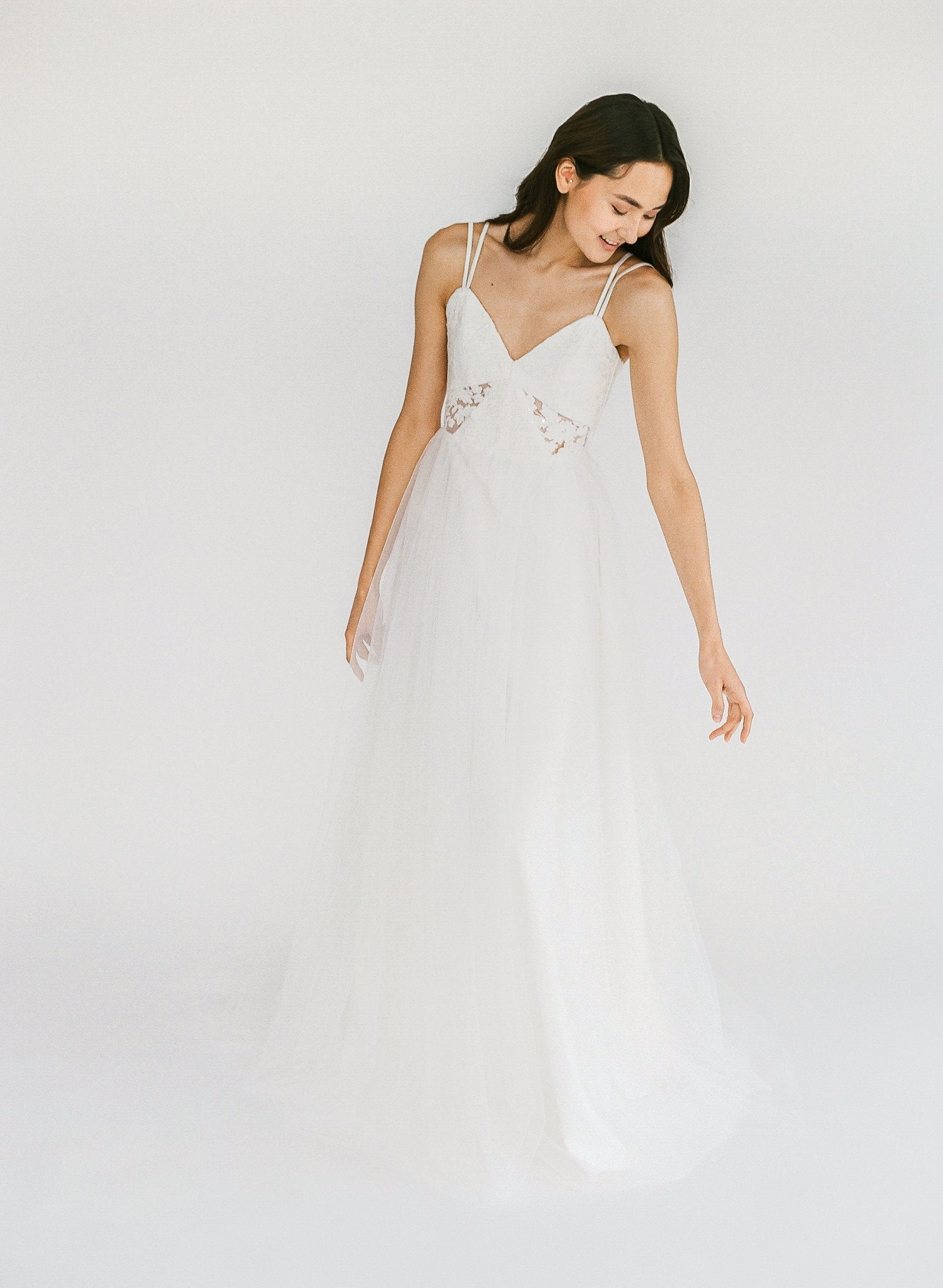 Unique non-traditional wedding gown with beaded lace, sheer geometric cutouts, comfortable double straps, and a tulle skirt