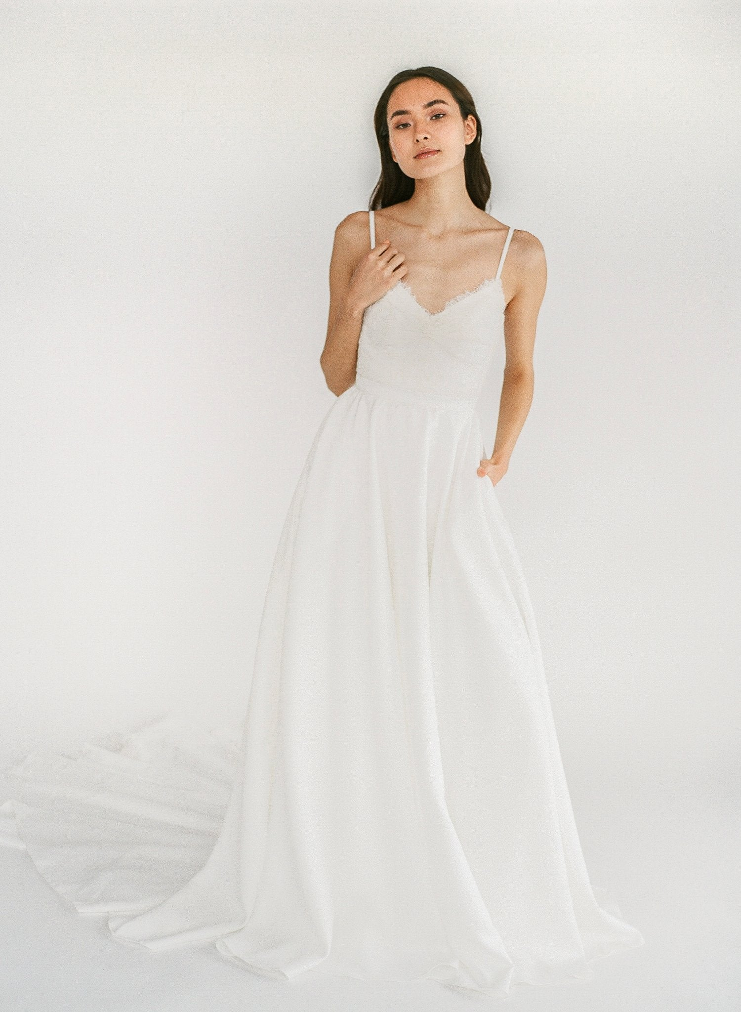 Romantic wedding dress with beaded lace, a button up back, and a crepe skirt with hidden pockets