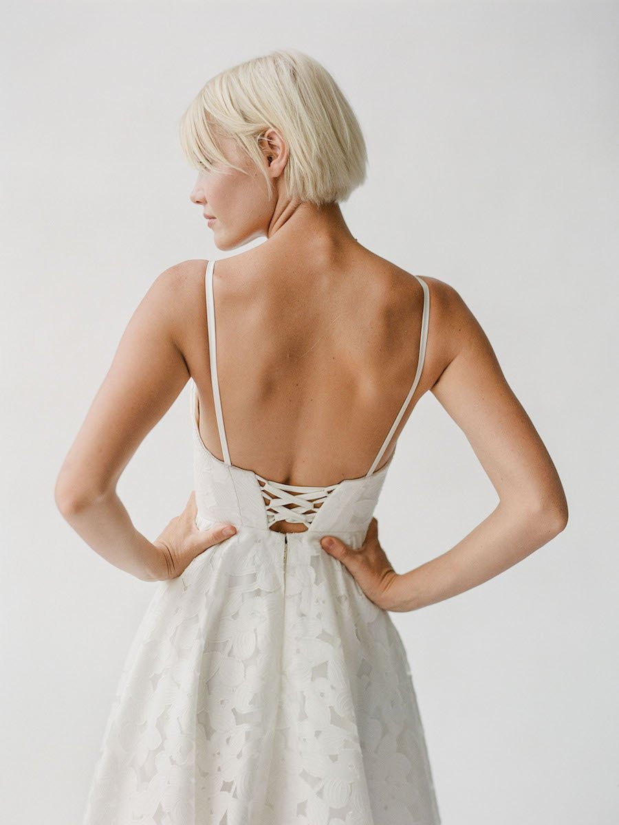 Structured wedding dress with floral lace and a low back with a lace-up corset tie
