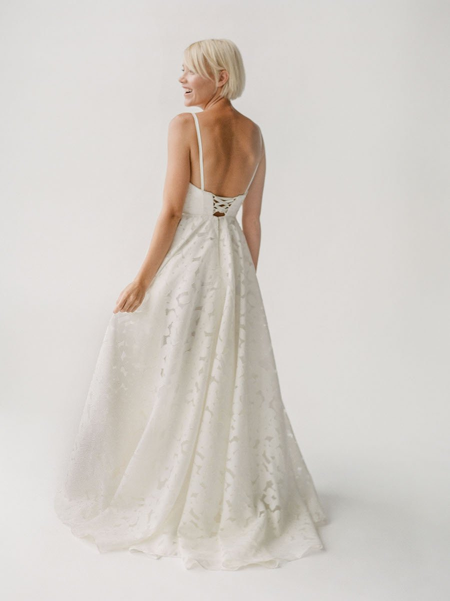Structured wedding dress with floral lace and a low back with a lace-up corset tie in Vancouver