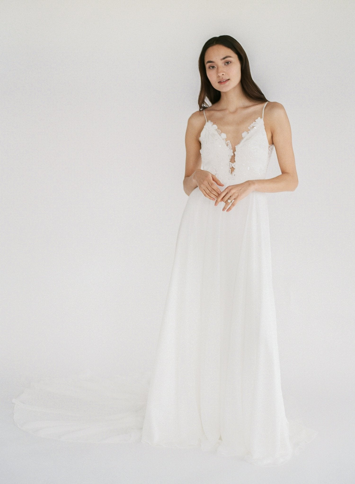 Flowy beach wedding dress with lace appliqué, a low back, and plunging neckline