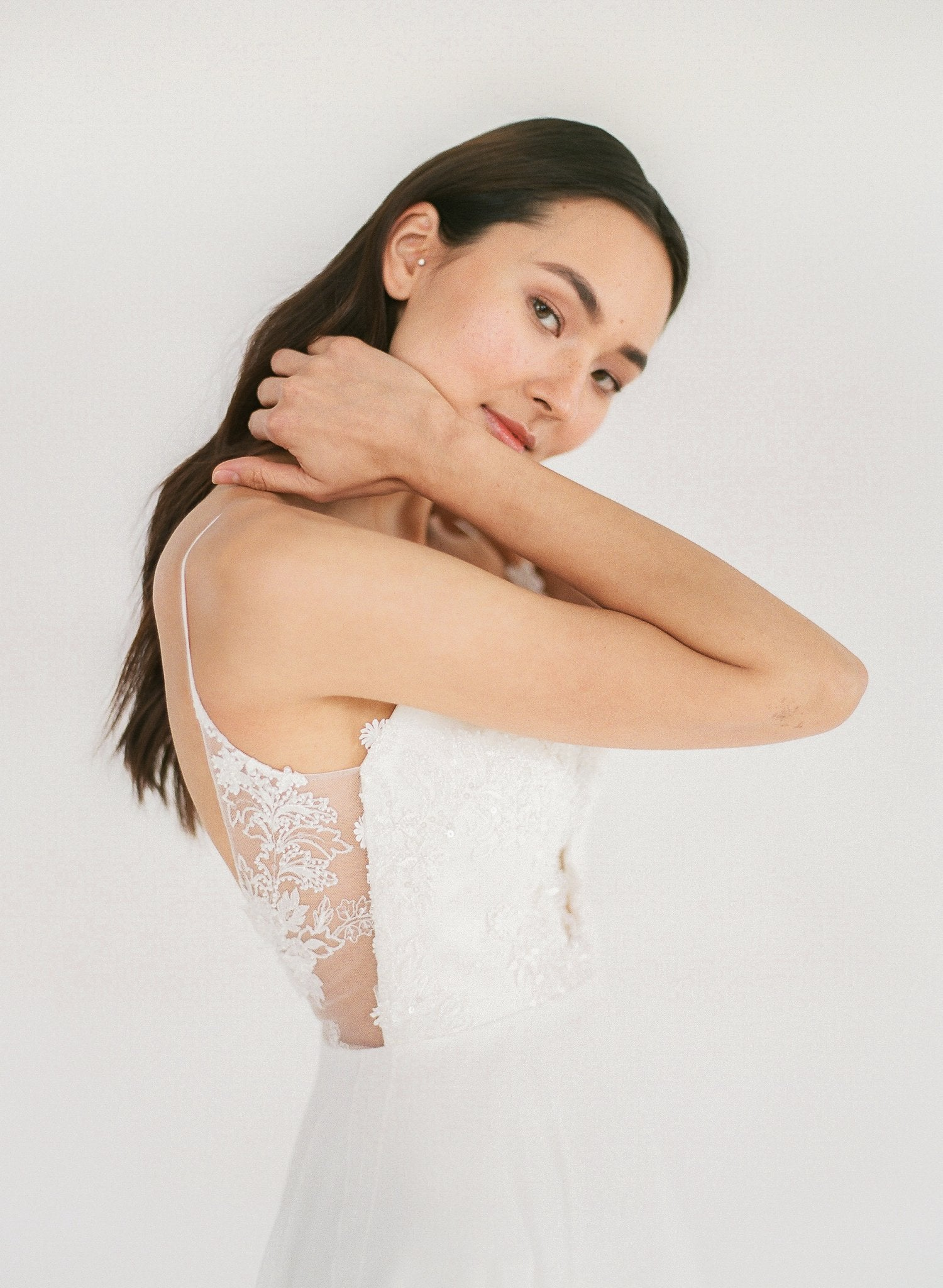 Ethically made flowy beach wedding dress with lace appliqué, a low back, and plunging neckline