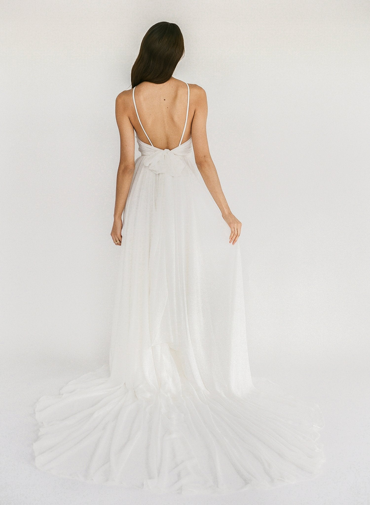A high neck beach wedding dress with a low back, chiffon ties, and a flowy skirt
