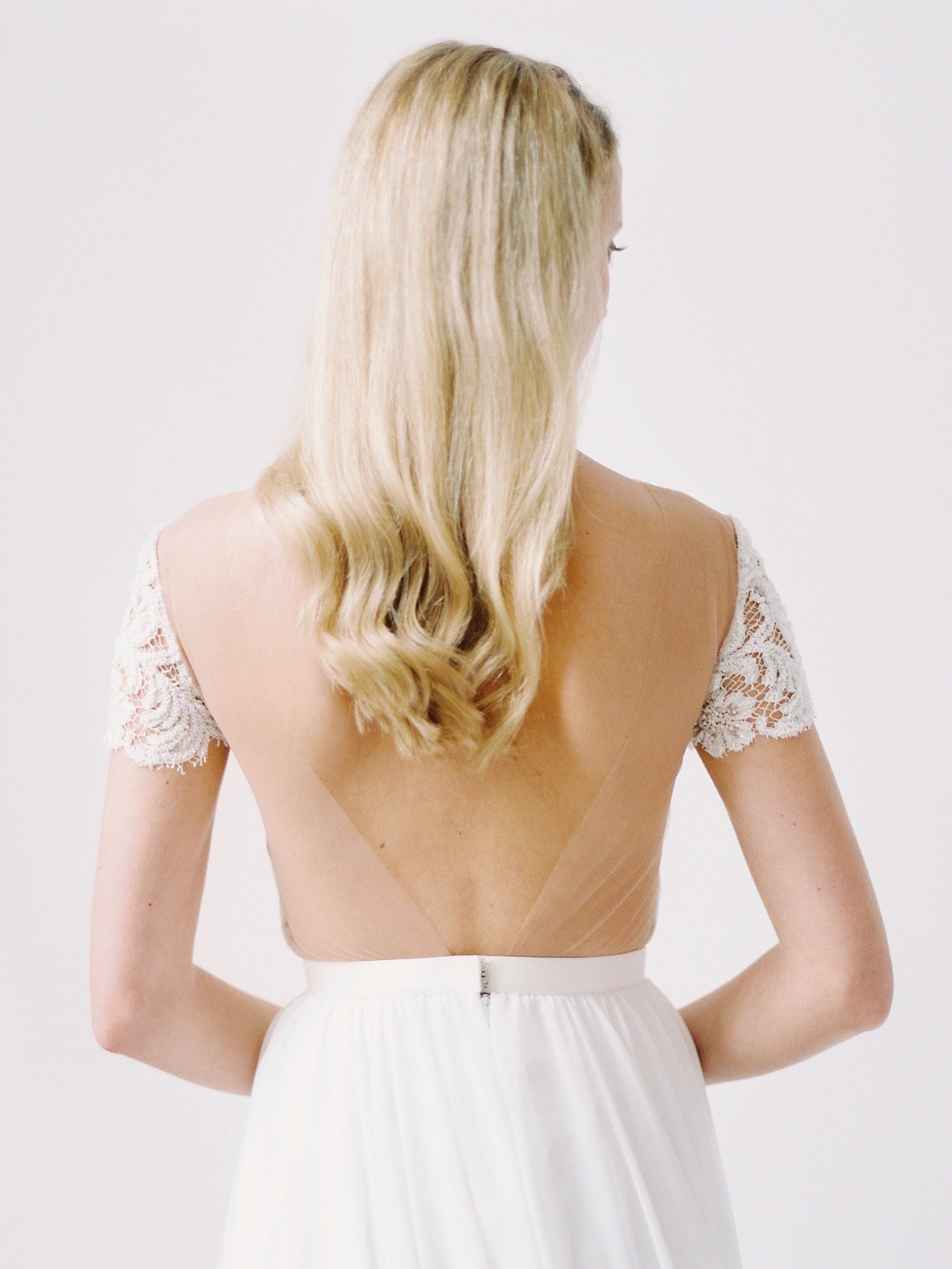 Romantic wedding dress with a wide open back and beaded cap sleeves