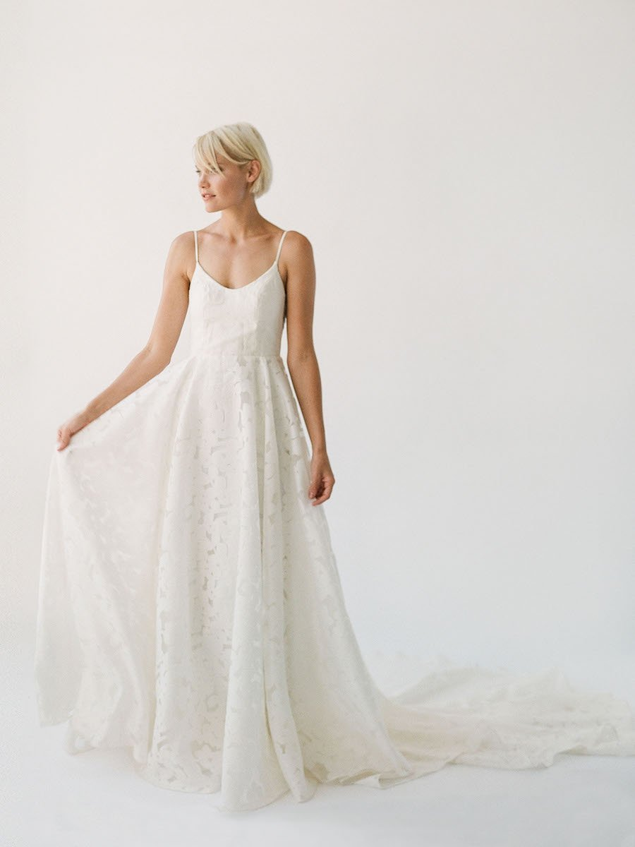 Simple and effortless wedding gown with sheer floral lace, a long train, and a low scoop back