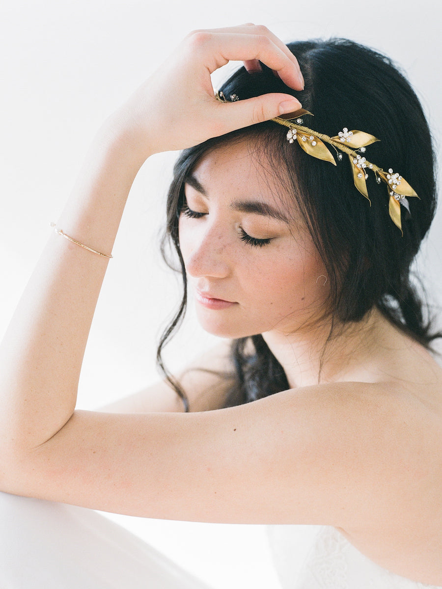 A golden headpiece with brass leaves, clear crystals, and pearl flowers.