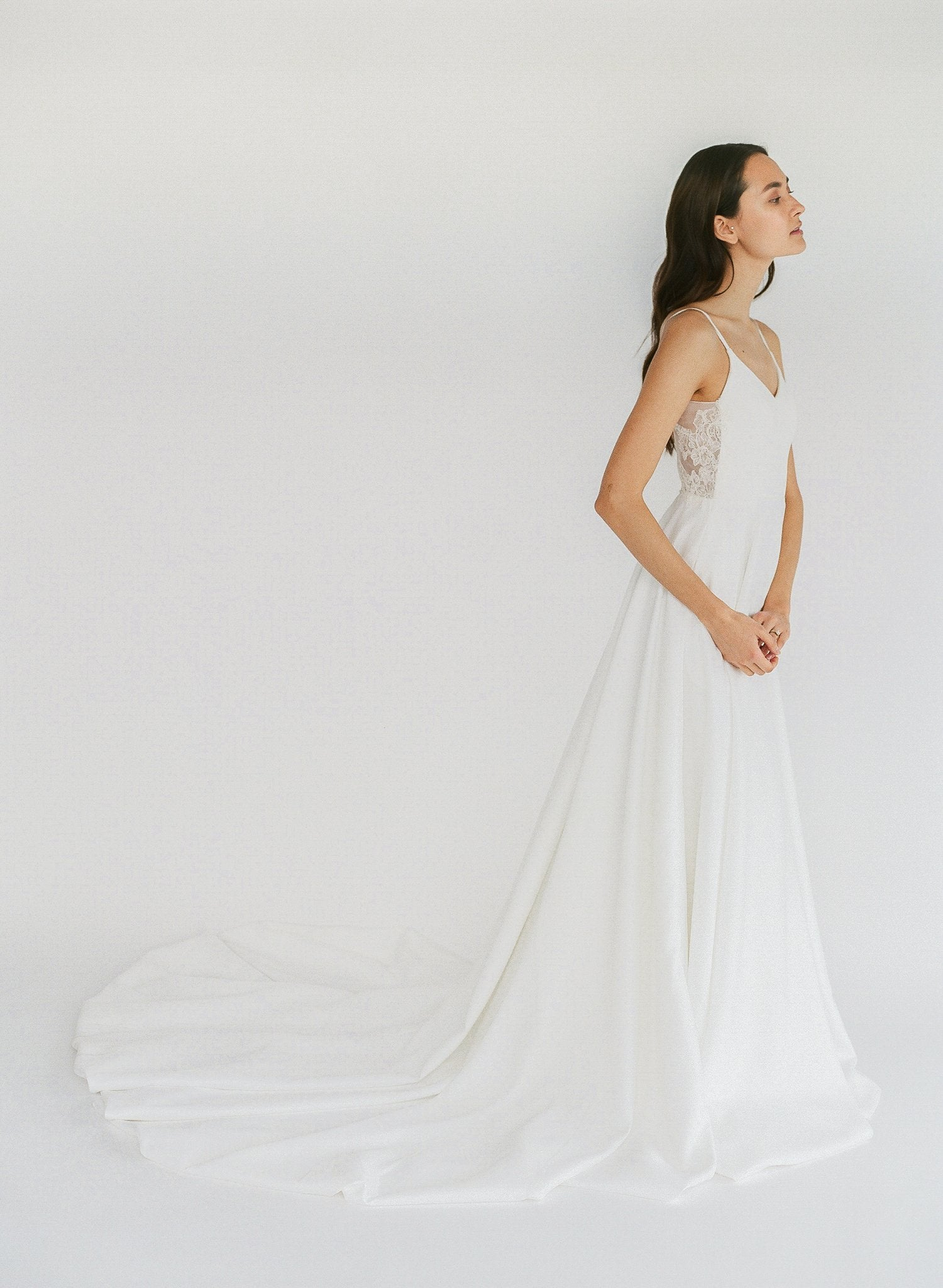 A simple low-back wedding dress in textured crepe fabric with appliqué lace and pockets