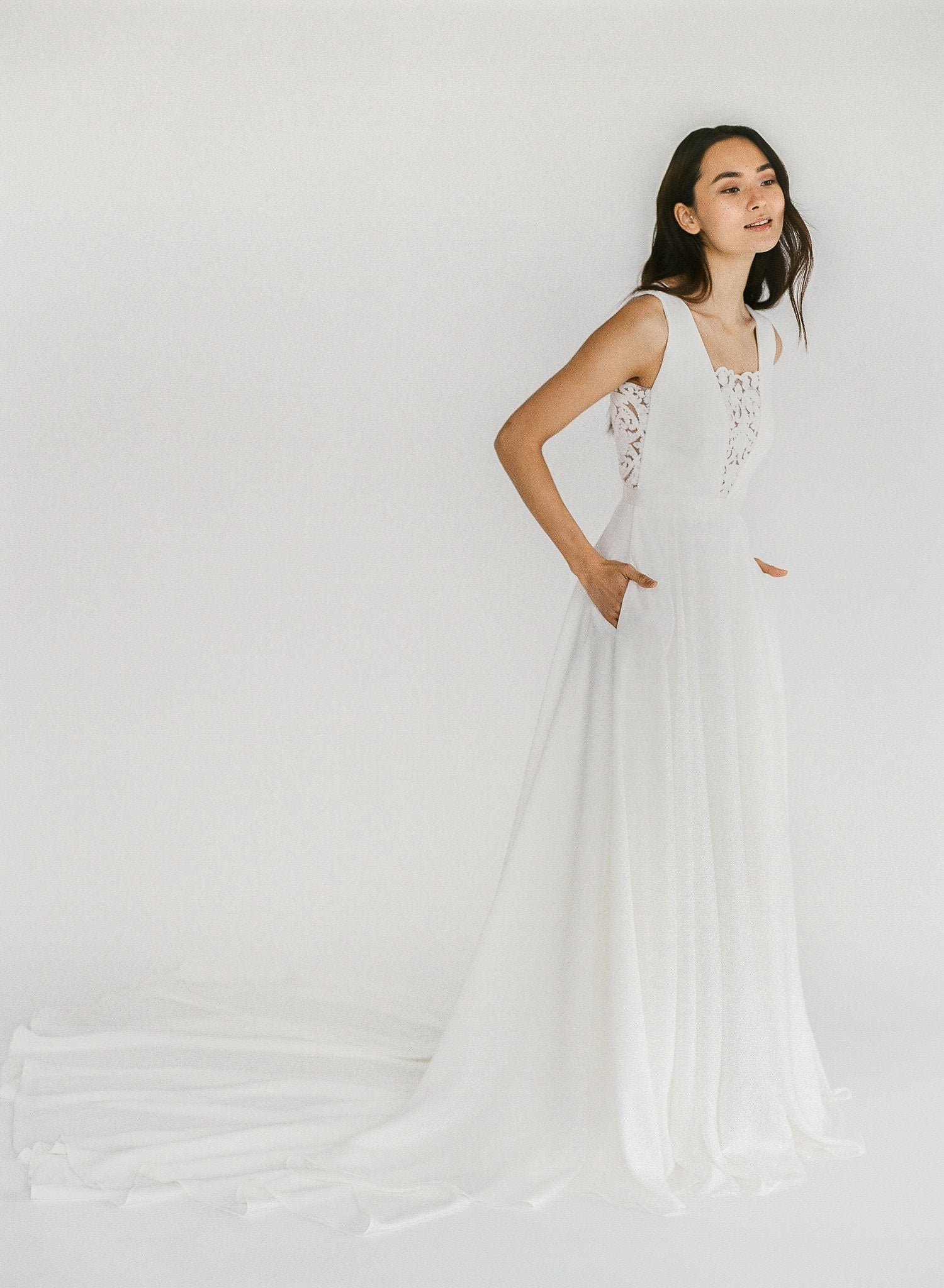 Ethical handmade elegant a-line crepe wedding dress with a low back, lace front, and pockets