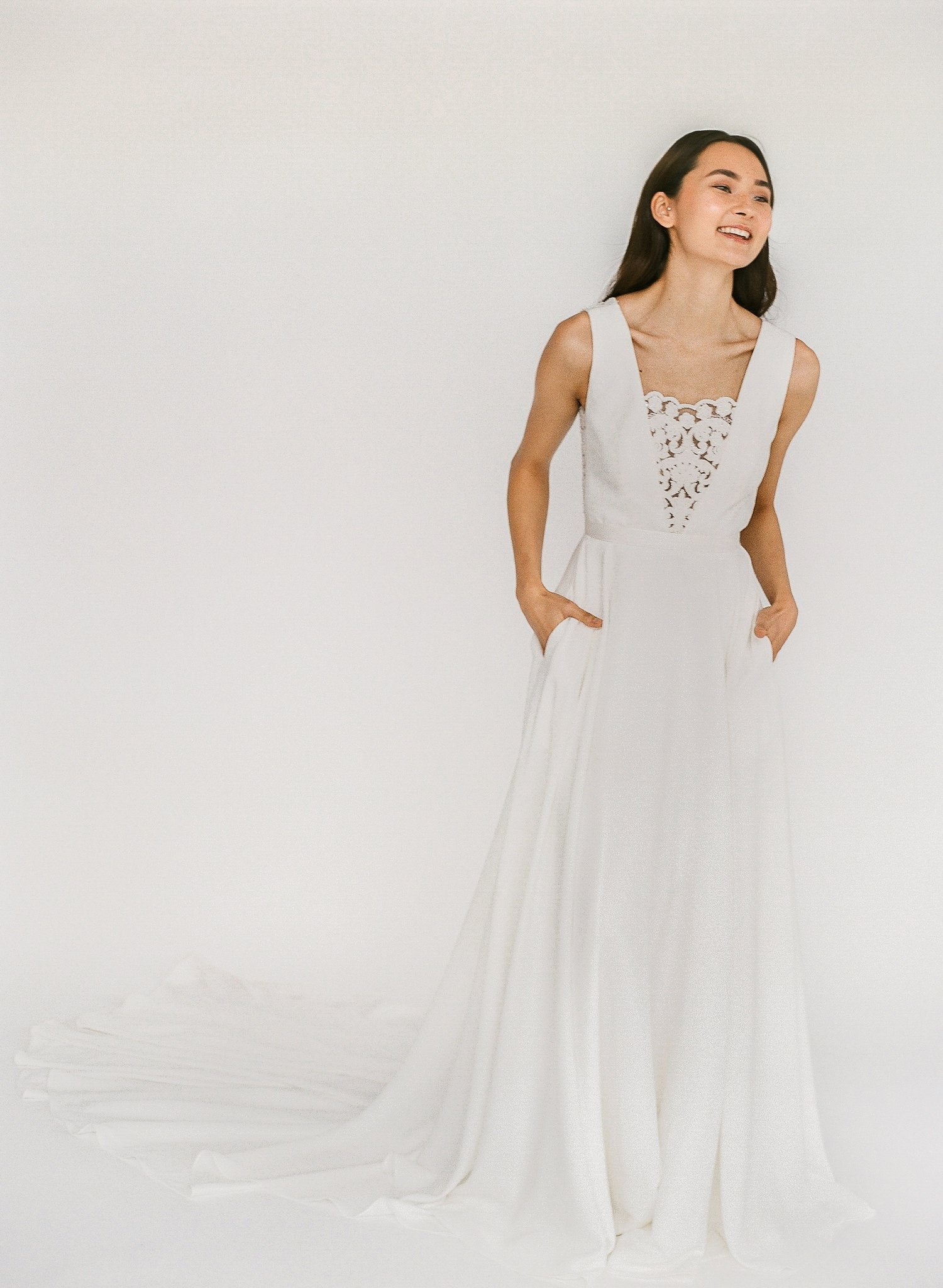 Elegant a-line crepe wedding dress with a low back, lace front, and pockets