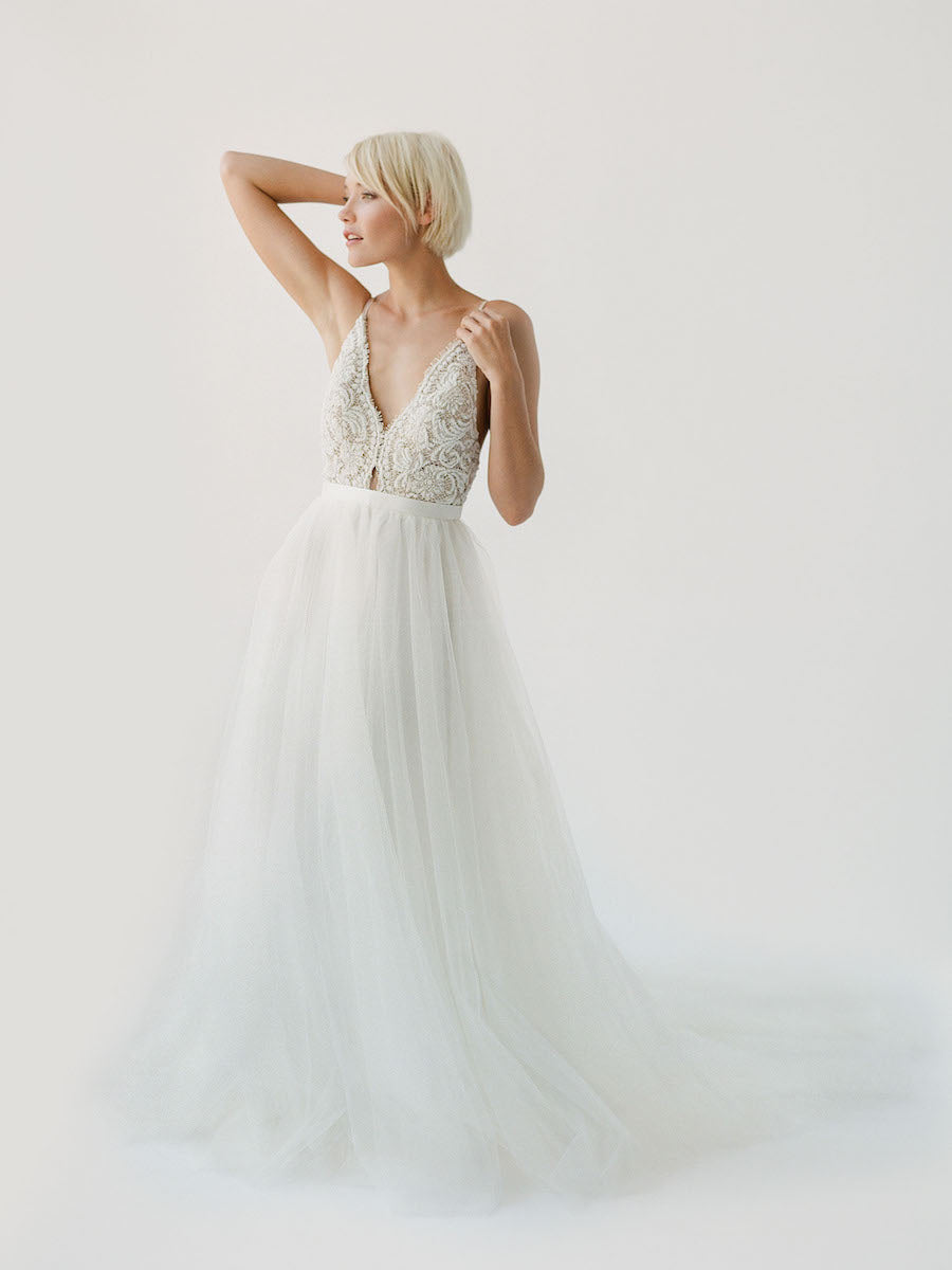 Champagne-toned wedding dress with white beading, an open back, and a soft princess tulle skirt