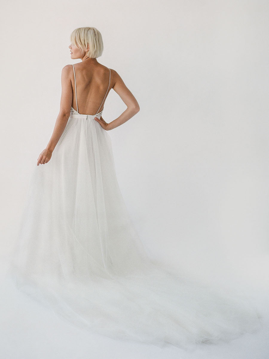 Comfortable champagne-toned wedding dress with white beading, an open back, and a soft princess tulle skirt