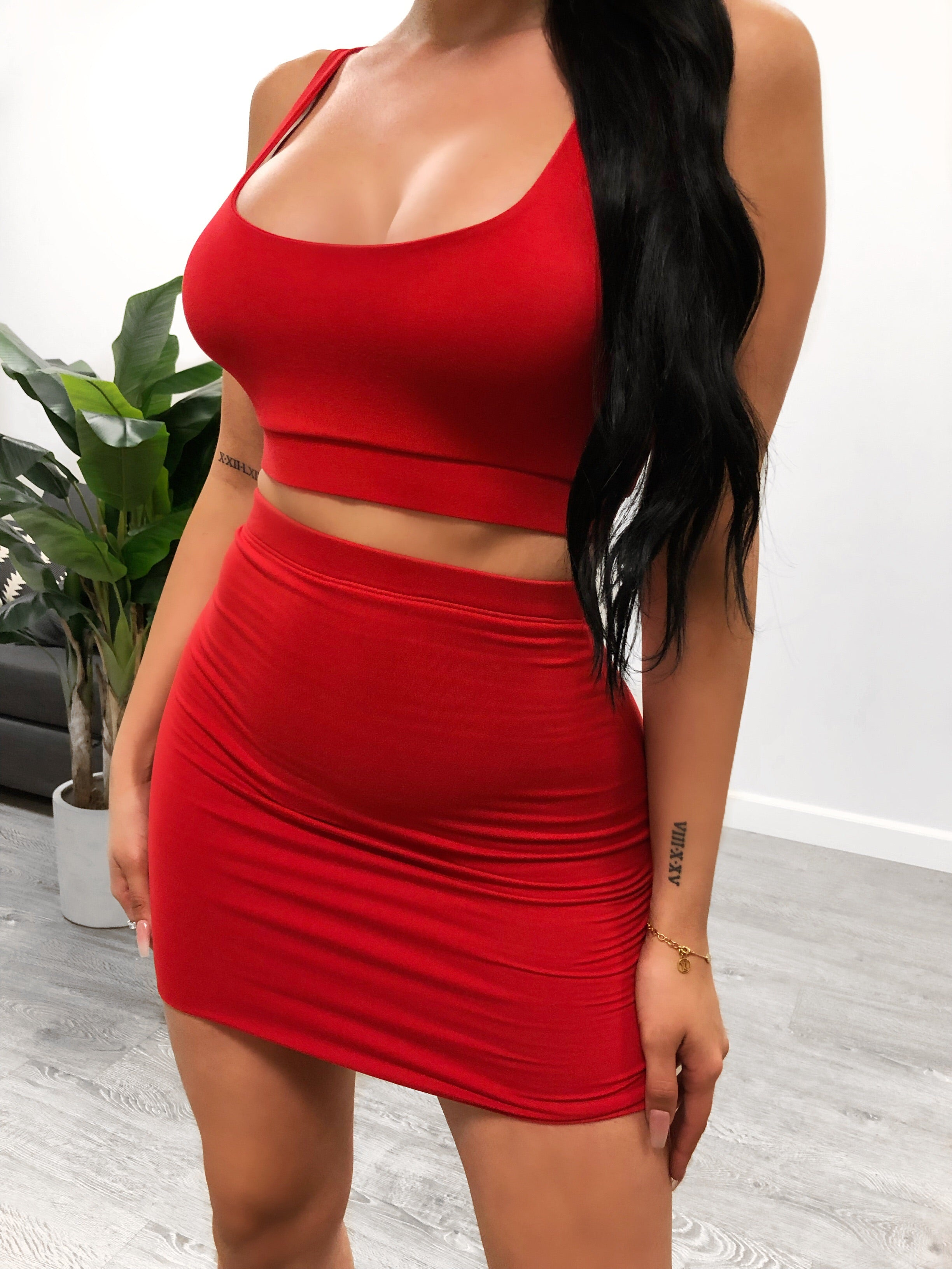 red two piece with a spaghetti strap tank top with a low u cut that shows mid cleavage. top length stops above belly button. bottoms are highways skirt that ends at mid thigh. material is stretchy.