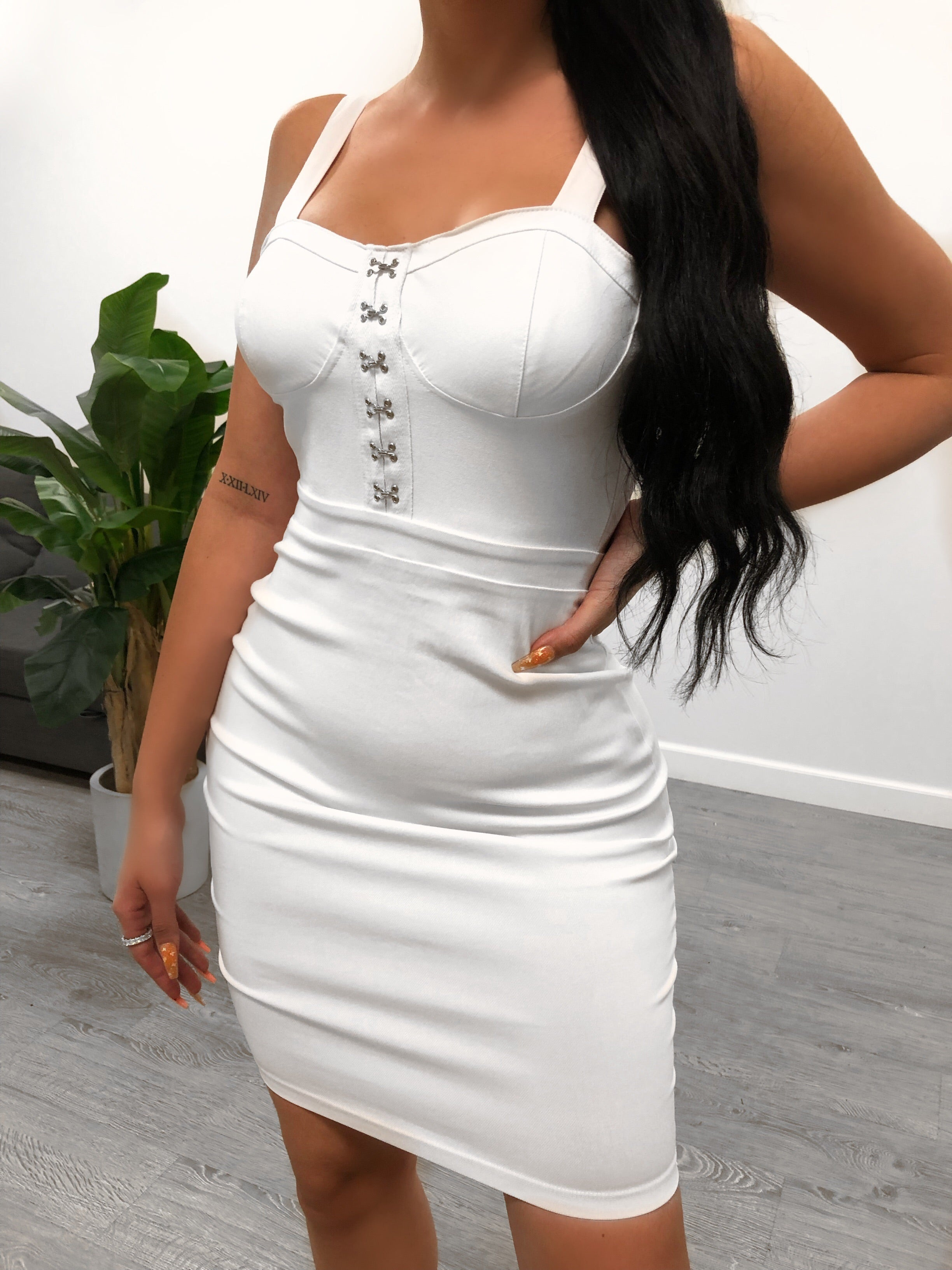 white night out dress. wide non adjustable straps. mid thigh/above the knee length. silver buckles on chest area for design..