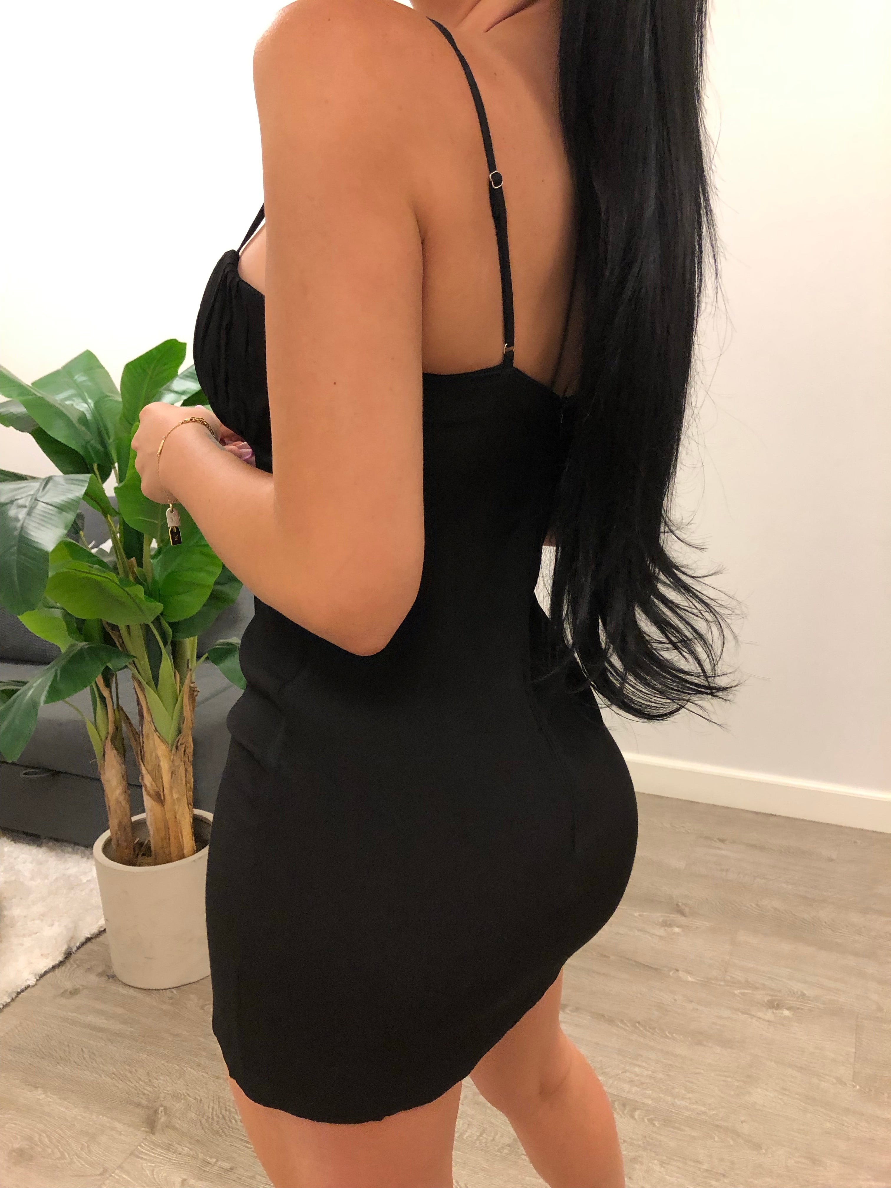 black color spaghetti strap dress with a short u shape to mid cleavage. dress is mid thigh length. has a small bow between cleavage and shows mid back