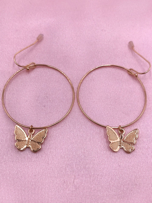 gold butterfly hoops with butterfly pendant .