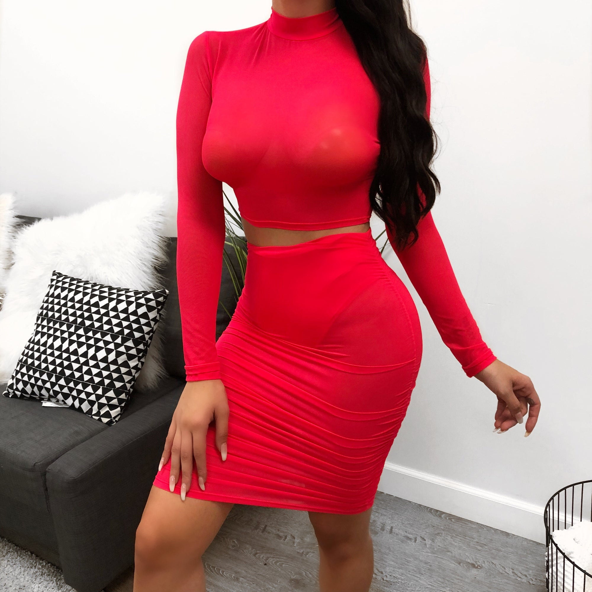 mesh neon pink two piece. long sleeve mesh top with funnel neckline. see through.  skirt is mesh and above the knee length. Undergarments not included.