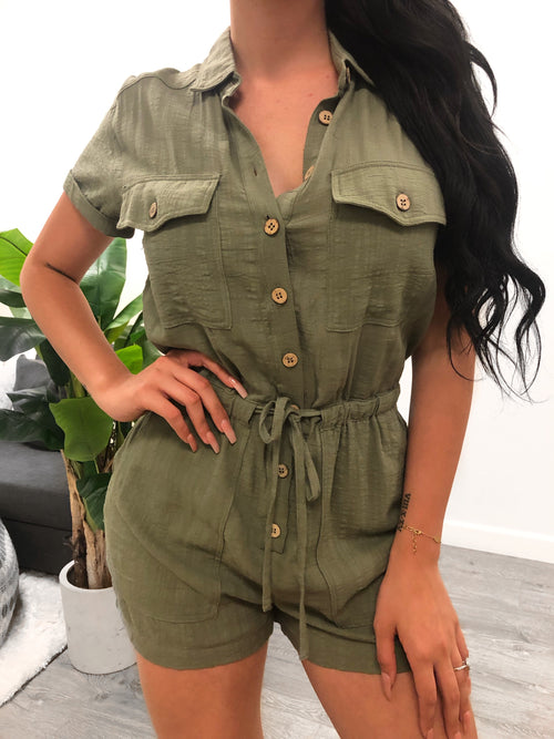 olive romper buttons from top to bottom. has a collar and pockets on sides. has strings in the middle tat adjust fitting.