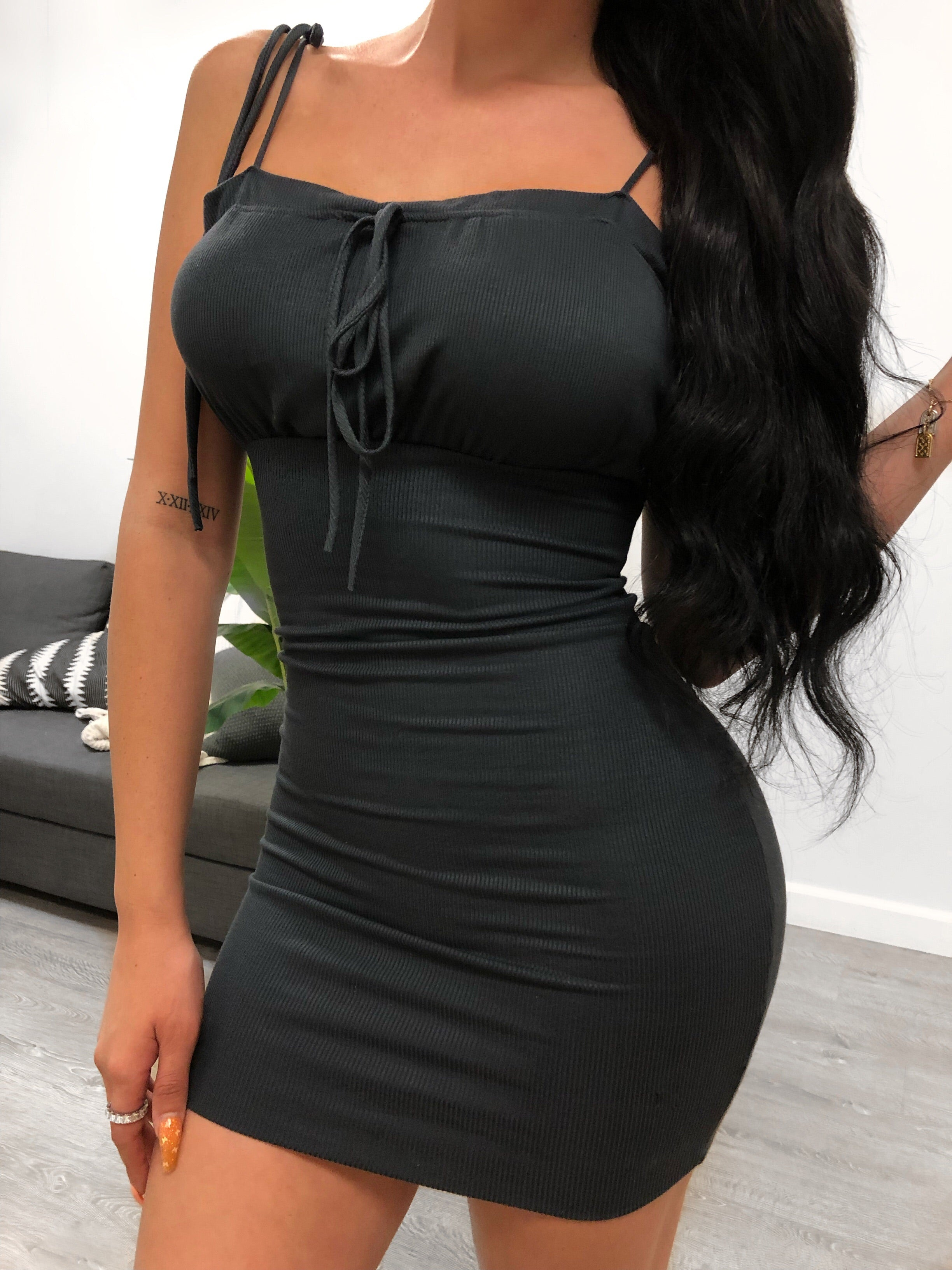 charcoal spaghetti strap dress. spaghetti straps have extra string to tie a bow. no cleavage visible. extra string at upper cleavage to tie a bow for style. dress length ends at mid thigh