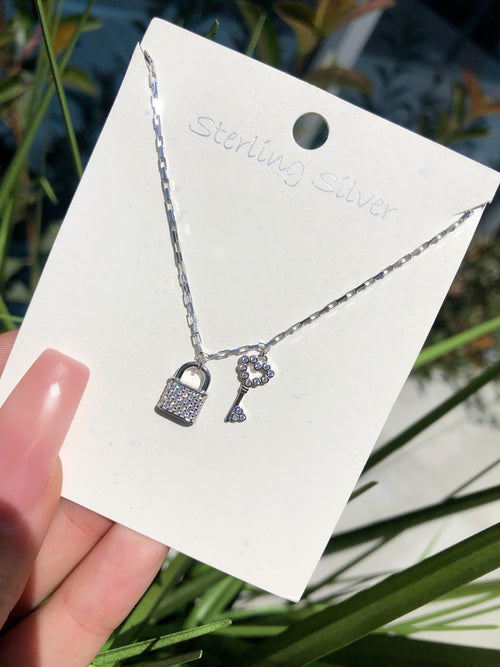 silver chain necklace with lock and key charms, charms have silver studs throughout them
