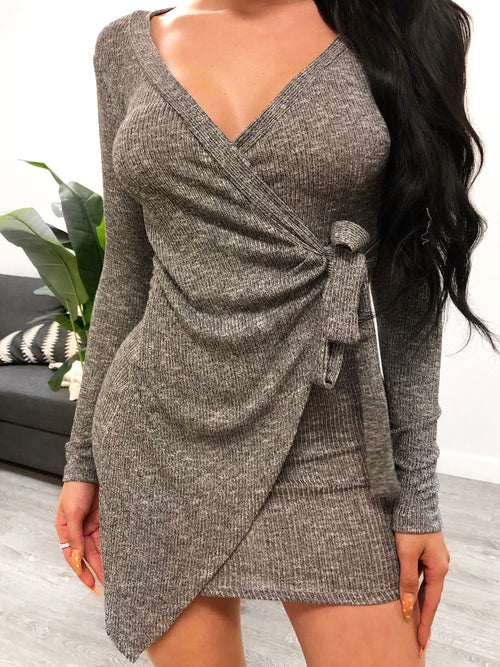Grey wrap around dress with long sleeves. low v cut cleavage. dress length ends at mid thigh