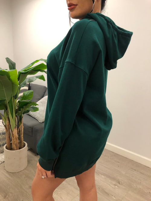 Dark emerald hoodie. Hoodie is long sleeve and runs mid-thigh length. Can be used as an oversized sweater or sweater dress. Has hoodie straps for decoration at the neck. Zipper adorns the thigh sides from waist to thigh. Hoodie is zipper removable.